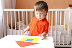 Baby constructing house of paper details Royalty Free Stock Images