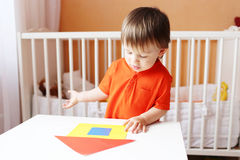 Baby constructing paper house Royalty Free Stock Photography