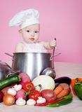 Baby cook. With vegetables in studio Stock Images