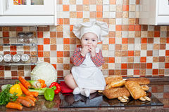 Baby cook with bread. And steering-wheels sits on a kitchen table Royalty Free Stock Photography