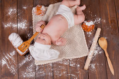 The baby cook flour buns bread. The baby in the head cook flour buns bread Royalty Free Stock Photo