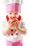 Baby cook girl wearing chef hat with fresh apple. Royalty Free Stock Image