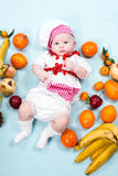 Baby cook girl wearing chef hat with fresh fruits. Royalty Free Stock Image