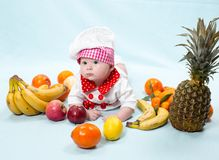 Baby cook girl wearing chef hat with fresh fruits. Royalty Free Stock Photo