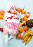 Baby cook girl wearing chef hat with fresh fruits. Stock Photography