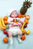 Baby cook girl wearing chef hat with fresh fruits. Royalty Free Stock Photos