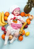Baby cook girl wearing chef hat with fresh fruits. Stock Photo