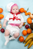 Baby cook girl wearing chef hat with fresh fruits. Stock Images
