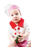Baby cook girl wearing chef hat with fresh vegetables and fruits. Royalty Free Stock Image
