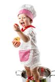 Baby cook girl wearing chef hat with fresh vegetables and fruits. Royalty Free Stock Images