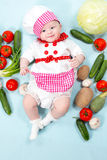 Baby cook girl wearing chef hat with fresh vegetables. Royalty Free Stock Images