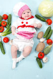 Baby cook girl wearing chef hat with fresh vegetables. Royalty Free Stock Photos