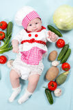 Baby cook girl wearing chef hat with fresh vegetables. Royalty Free Stock Photo