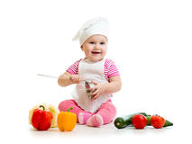 Baby in cook hat with healthy food vegetables stock photo