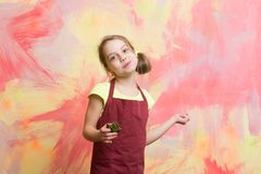 Baby cook in red chef apron on colorful abstract wall. Happy child smiling with cake. Baking and delicious bakery. Healthy food and diet concept. Girl eating Royalty Free Stock Photos