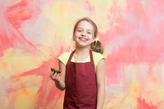 Baby cook in red chef apron on colorful abstract wall. Girl eating cupcake. Baking and delicious bakery. Happy child smiling with cake. Healthy food and diet Royalty Free Stock Photography
