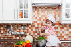 Baby cook with vegetables Royalty Free Stock Images