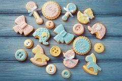 Baby cookies decorated with glaze. On wooden background Royalty Free Stock Images