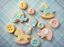 Baby cookies decorated with glaze. On color background Stock Photos