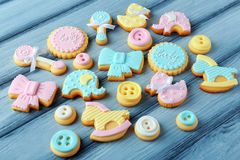 Baby cookies decorated with glaze. On wooden background royalty free stock photo