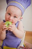 Baby cooking at the kitchen eating apple. Little boy in a purple chief hat and aprons sitting on a floor and eating green apple Royalty Free Stock Photography
