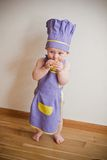 Baby cooking at the kitchen eating apple. Little boy in a purple chief hat and aprons standing on a floor and eating green apple Royalty Free Stock Photo