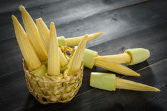 Baby corn in a basket. On a wooden table Stock Photography