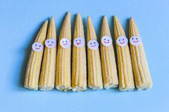 Baby corn with funny faces. Healthy organic food