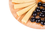 Baby corn and olives on platter. Stock Photos
