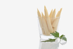 Baby corns in glass with parsley on white background Stock Photography