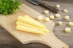 Baby corns and knife on cutting board,food ingredient. Baby corns and knife on cutting board Royalty Free Stock Photos