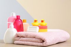 Baby cosmetic products, toys and towel on table against color. Background stock images