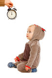 Baby in costume looking on alarm clock Stock Photos