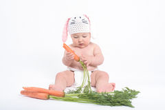 Baby in a costume of rabbit nibbling carrot Stock Photography