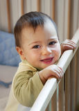 Baby in cot. Portrait of 9 month old baby, boy or girl  standing in his cot, smiling , looking into the camera Royalty Free Stock Photos