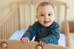 Baby in cot. Cute happy 8 month old baby, boy or girl  standing in wooden cot or crib Royalty Free Stock Image
