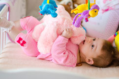 Baby in a cot. Little cute baby girl playing in a cot Stock Photography