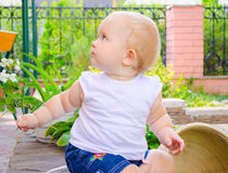 Baby in courtyard. Beautiful baby girl sitting among the flowers in courtyard stock image
