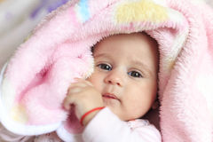 Baby covered in pink blanket Stock Images