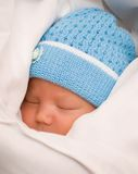 Baby in coverlet Stock Images