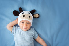 Baby in a cow hat on blue blanket Royalty Free Stock Image