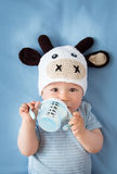 Baby in a cow hat drinking milk Royalty Free Stock Photography