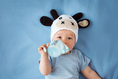 Baby in a cow hat drinking milk Stock Photography