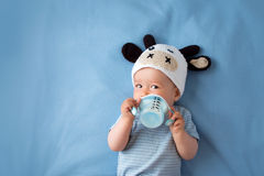Baby in a cow hat drinking milk Stock Photos