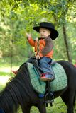 Baby cowboy. Cowboy child sit on horse in hat Royalty Free Stock Photography