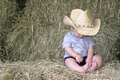 Baby cowboy in the hay. A baby boy sitting on hay bales wearing a cowboy hat Stock Image