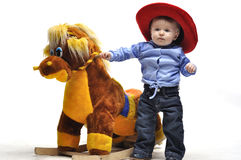 Baby in cowboy style stay before toy horse. In studio Stock Photo