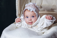 Baby in cradle. Cheerful and happy blue-eyed baby in  bonnet lies in cradle Stock Photography