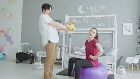 Baby crap one`s pants during mom`s sport exercises stock video