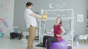Baby crap zijn broek tijdens de sportoefeningen van het mamma stock video